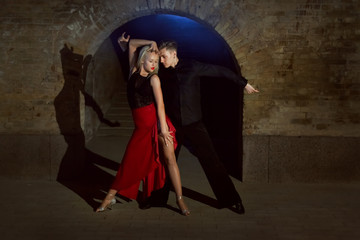 Two young and beautiful dancers perform the tango. Latin American dances.