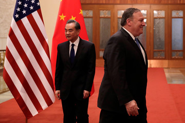 U.S. Secretary of State Mike Pompeo walks by Chinese Foreign Minister Wang Yi as they head to their meeting at the Great Hall of the People in Beijing