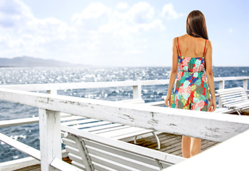 Slim young woman on white pier and sea landscape