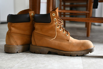A pair of recently used beige leather hiking boots belonging to a stylish individual who may enjoy outdoors wilderness activities or just fashion sit on a kitchen floor next to the legs of a dining ta