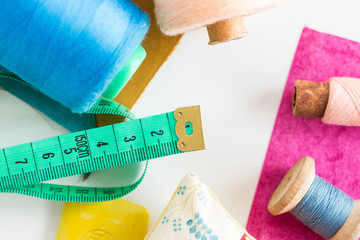 sewing, patchwork and tailoring concept - closeup on measuring meter, blue and pink threads in bobbins and purple and mustard color patches on white background, top view, flat lay.