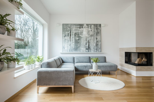 Spacious white living room interior with grey corner couch, big modern art painting and fireplace