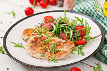 Grilled chicken fillet and fresh vegetable salad of tomatoes,red onion and arugula. Chicken meat salad. Healthy food.