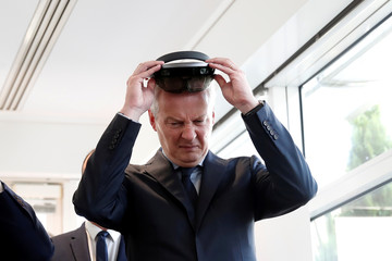 French Finance Minister Bruno Le Maire holds a virtual reality headset during a visit of the new Qwant headquarters in Paris