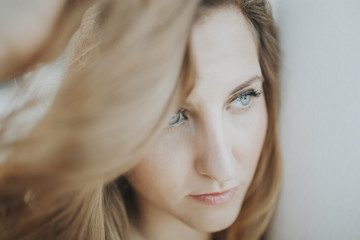 Blonde white woman face close up portrait. She has clear beautiful blue eyes.