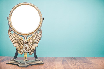 Old antique vintage cast iron desk makeup mirror frame blank in the form of goddess with wings or angel standing on table front turquoise wall background. Circa 1800s or early 1900s. Retro style photo