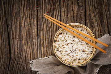 Bowl with boiled rice on a wooden background. Vegan food. Dietary meal. Top view. Flat lay