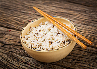 Bowl with boiled rice on a wooden background. Vegan food. Dietary meal