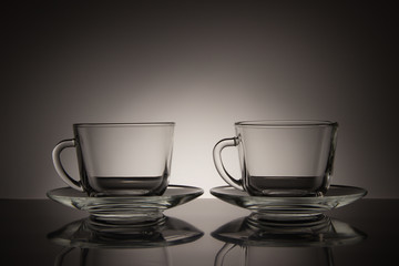 Two glass for tea and an empty saucer on a black and white background