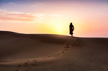 Woman in the desert with sunset view