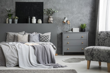 Grey armchair near cabinet and bed with sheets in bedroom interior with black poster. Real photo