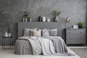 Pillows on bed between table and cabinet in bedroom interior with concrete wall. Real photo