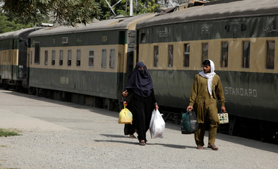 Passengers arrive to board a train as they travel home ahead of the upcoming Eid al-Fitr holiday, marking the end of the Muslim holy month of Ramadan, at a railway station in Rawalpindi