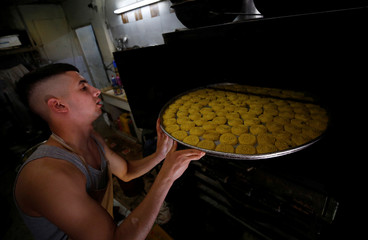 Palestinian man prepares traditional cakes at a sweet shop ahead of the Eid al-Fitr holiday marking the end of the Muslim holy month of Ramadan, in the old city of Nablus in the occupied West Bank