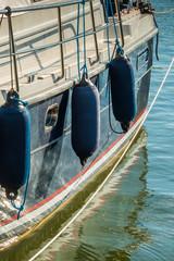 Luxus-Segelboot im Hafen mit Fendern, über dem Meer.