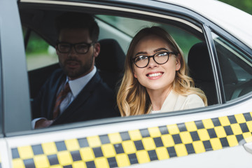 smiling young woman in eyeglasses looking at window while sitting with handsome man in taxi