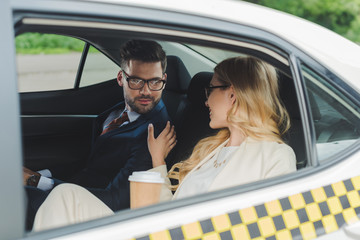 smiling young woman holding paper cup and flirting with handsome man sitting in taxi