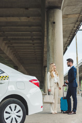 stylish young couple talking and looking at each other while standing with suitcase near taxi