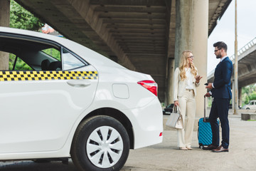 stylish young couple talking and looking at each other while standing with suitcase near taxi cab