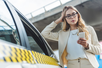 beautiful fashionable blonde girl in eyeglasses leaning at taxi cab and using smartphone