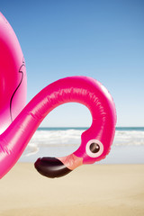 pink flamingo swim ring on the beach