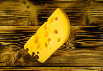 Piece of cheese on wooden table. Top view