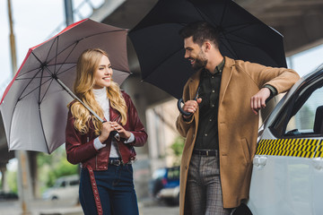 happy young couple holding umbrellas and smiling each other while standing together neat taxi car