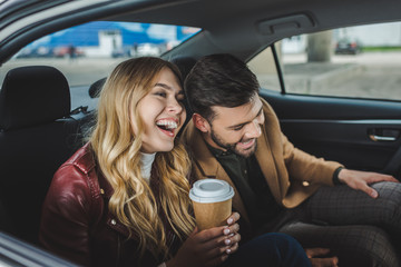 happy young couple laughing while sitting together in taxi
