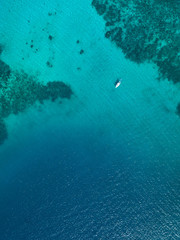 Top down aerial drown view of a small boat over a tropical coral reef in a clear ocean