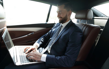 Businessman working with laptop sitting in car