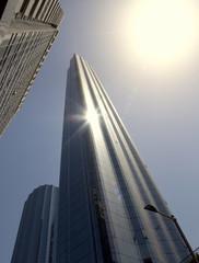 Steil in den Himmel ragender Wolkenkratzer im gleisenden Sonnenlicht