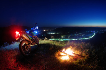 Motorcycle at night standing near fire flame above the valley of the Katun river view from the top hill to the bright sunset trails road