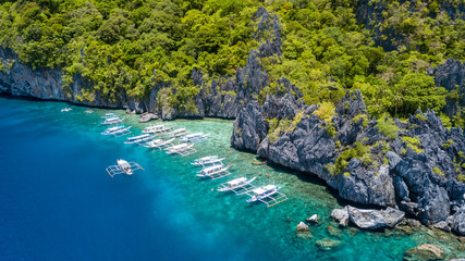 Aerial drone view of tourist boats over a tropical coral reef and small sandy because in the Bacuit Archipelago