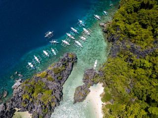 Aerial drone view of banca boats over a beautiful shallow tropical lagoon with sandy beach
