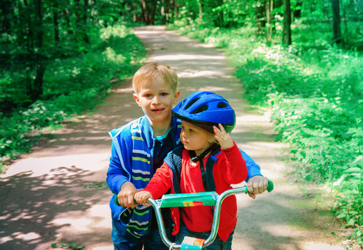 big brother helping little sister to ride bike in nature