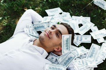 Handsome young man in a white shirt lies on the ground covered with American dollars