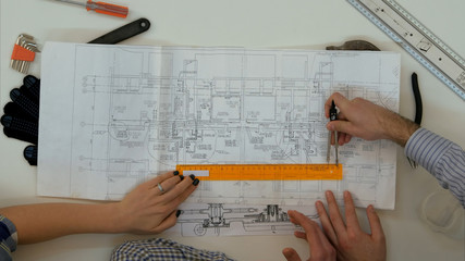 Young architects checking drawing measurements with divider and ruler