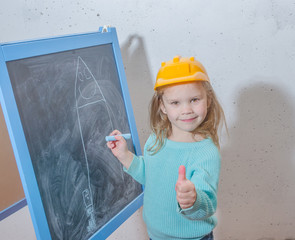 girl in a helmet paint a house on a chalk Board