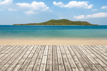 Wooden floor on beach with mountain and cloudy background. For your product placement or montage with focus to the table top in the foreground. Empty wood white shelf. shelves