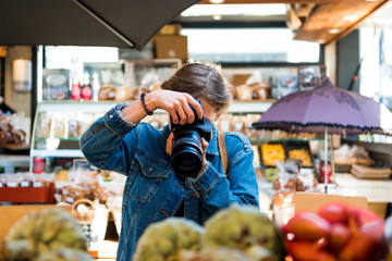 woman with obscured face by camera taking picture in shop