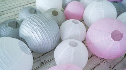 Colorful white pink gray paper lanterns set on floor. Decorating wedding banquet hall interior.