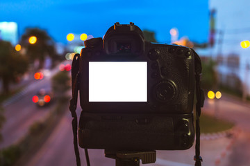Close-up of DSLR Camera capturing on colorful light abstract circular bokeh background,Night time,Mockup image of with blank screen,DSLR on Tripod.