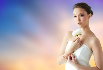 beauty, jewelry, people and luxury concept - beautiful asian woman or bride in white dress with peony flower, golden ring and bracelet over pastel background