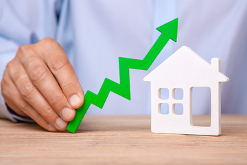 Rising house prices. Man is holding green arrow up in his hand and house