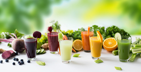 healthy eating, drinks, diet and detox concept - glasses with different fruit or vegetable juices...