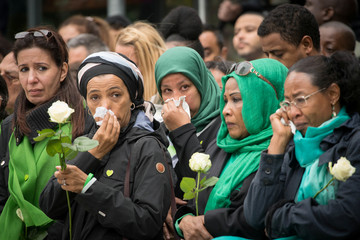 People attend the Grenfell Tower anniversary national minute silence and mosaic unveiling at the base of Grenfell Tower to mark a year since the fire which claimed 72 lives, in west London