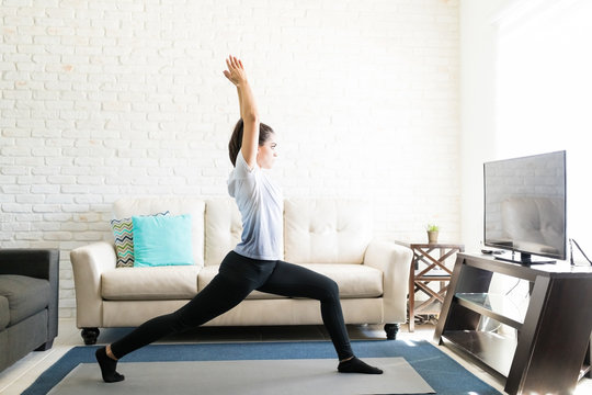 Woman doing stretching yoga poses at home