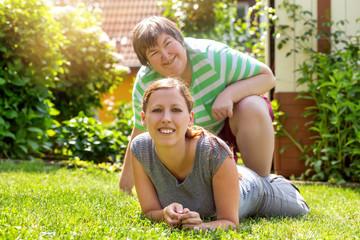 Geistig behinderte Frau und Behindertenhilfe oder Betreuerin im Garten