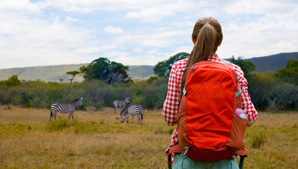 adventure, travel, tourism, hike and people concept - young woman with backpack over zebras in african savannah background