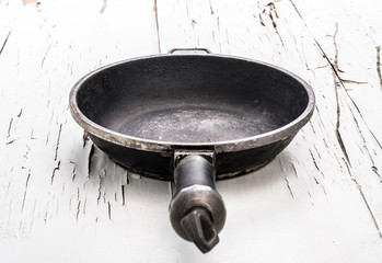 Empty old cast iron frying pan on white surface with cracked paint background